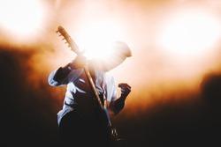 Silhouette of guitar player / guitarist perform on concert stage. Dark background, smoke, concert  spotlights