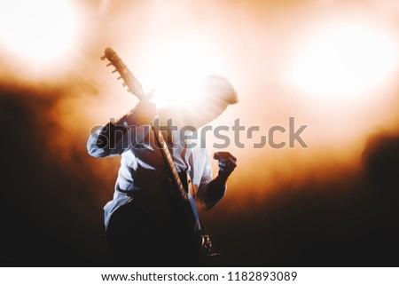 Silhouette of guitar player / guitarist perform on concert stage. Dark background, smoke, concert  spotlights #1182893089