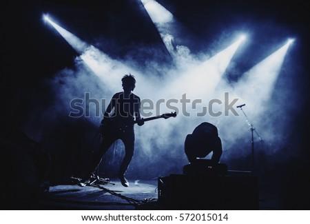 Silhouette of guitar player / guitarist perform on concert stage. Dark background, smoke, concert  spotlights #572015014