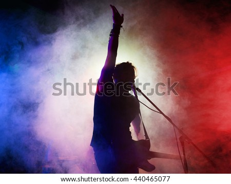 Silhouette of guitar player on stage. Dark background, smoke, spotlights #440465077