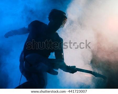 Silhouette of guitar player on stage. Dark background, smoke, spotlights Stock photo ©