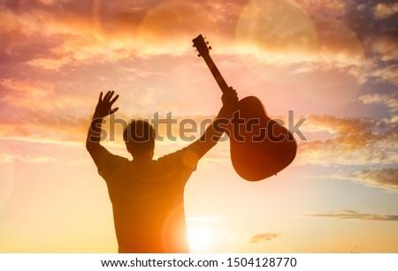 Silhouette of guitarist musician holding guitar against sunset concept for religion or music festival