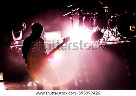 Silhouette of guitarist musician on stage at a concert.   #593999426