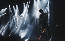 Silhouette of guitarist perform on concert stage. Dark background, smoke, concert  spotlights