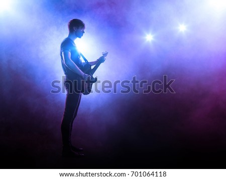 Silhouette of guitarist playing solo on stage on blue background with smoke and spotlights