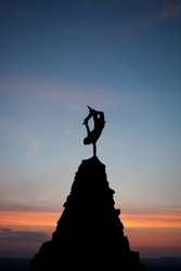 silhouette of gymnast on top of pyramid