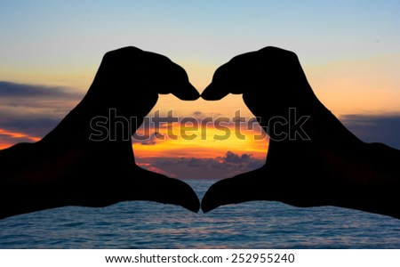 Silhouette of hand heart sign with sea and sunset background