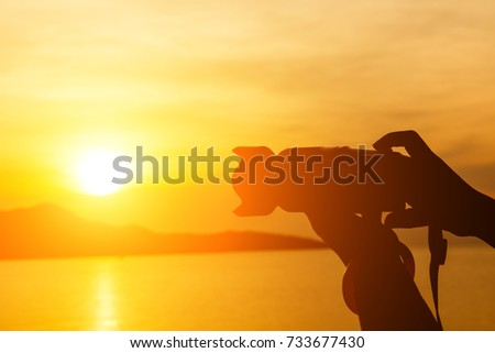 Silhouette of hand photographer and camera  taking pictures of mountain view with sunset #733677430