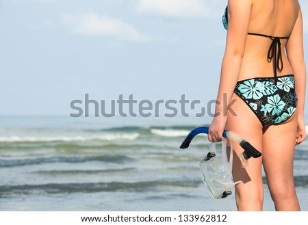 Silhouette of hand with equipment for snorkeling, on the beach (picture with space for text)