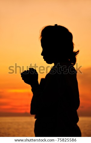 Silhouette of hands clasped in praying against sunset