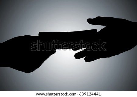 Silhouette Of Hands Giving Bribe Against Gray Background ストックフォト ©