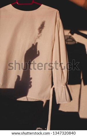 Silhouette of hands holding cane on blouses hanging on a red hanger. Fashion content. Shadow on shirt and wall. Details of everyday elegant look. Street fashion for spring, summer or fall season.