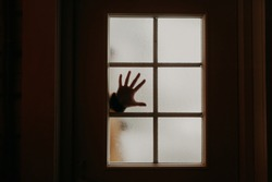 silhouette of hands on glass at the door.