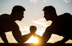 Silhouette of hands that compete in strength. Rivalry, closeup of male arm wrestling. Men measuring forces, arms. Two men arm wrestling. Rivalry, vs, challenge, hand wrestling. Sunset, sunrise.
