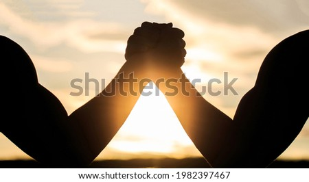 Silhouette of hands that compete in strength. Rivalry, closeup of male arm wrestling. Men measuring forces, arms. Two men arm wrestling. Rivalry, vs, challenge, strength comparison. Sunset, sunrise. Сток-фото ©