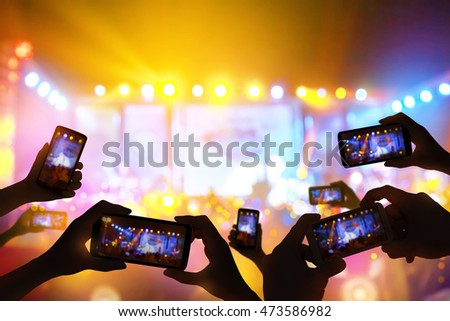 Silhouette of hands using camera phone to take pictures and videos at live concert,  smartphone records live music festival, Take photo in front concert stage, happy youth, luxury party.