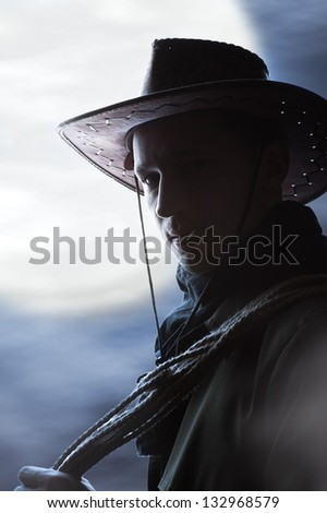 silhouette of Handsome man in cowboy costume stay in steppe at night with full moon. Vampire Hunter