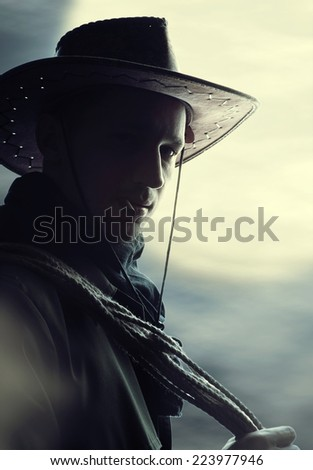 Stock Photo silhouette of Handsome man in cowboy costume stay in steppe at night with full moon. Vampire Hunter