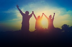 Silhouette of happiness teamwork hold hands up as a business successful, achieve business goal