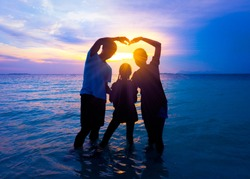 Silhouette of happy Asian family in love on vacation and Happy valentines day. Dad and mom making heart shape sign pass sun beams stand on tropical beach with sunset sky background. family concept.