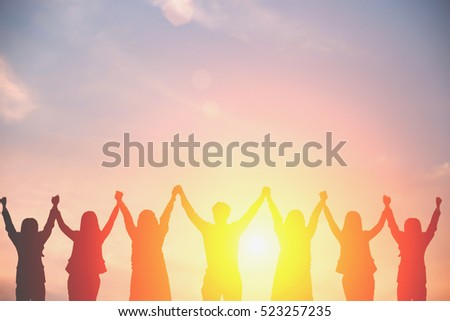 Silhouette of happy business team making high hands in sunset sky background for business teamwork concept.
