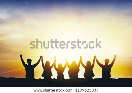 Silhouette of happy business teamwork making high hands over head in sunset sky evening time background as business successful,victory, business teamwork concept and freedom .