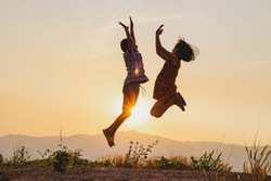 Silhouette of happy children jumping playing on mountain at sunset time