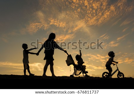 Silhouette of happy family, Little boy with small child in the stroller walking down the road and little boy riding bike having fun at sunset