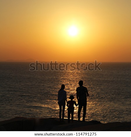 Silhouette of happy family walking on beach together at sunset