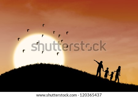 Silhouette of happy family walking up the hill with sunset scene