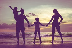 Silhouette of happy family who standing on the beach at the sunset time. People having fun on the sea. Concept of friendship forever and of summer vacation.