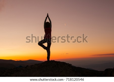 Silhouette of happy joyful young attractive woman playing yoga and having fun at the mountain against the sunset. Freedom, sport, adventure and leisure vacation concept.