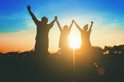 Silhouette of happy success positive teamwork hold hands up as business successful, business victory & celebrate achievement. Accomplish people merger & acquisitions concept.