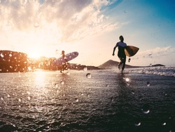 Silhouette of happy surfers running with surf boards on the beach - Sporty people having fun in sunny day - Extreme sport, travel and vacation concept - Focus on right male body