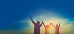 Silhouette of happy teamwork hold hands up as a business successful, business victory, achieve business goal