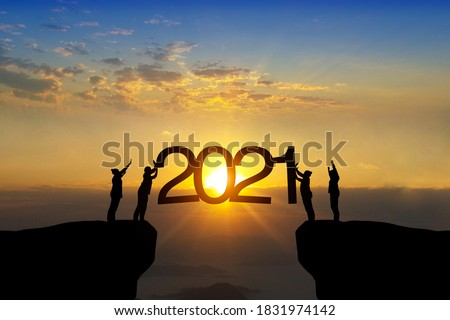 Silhouette of happy teamwork standing and touch 2021 text on beautiful sunrise backgroud celebrate business success and growth to year 2021.