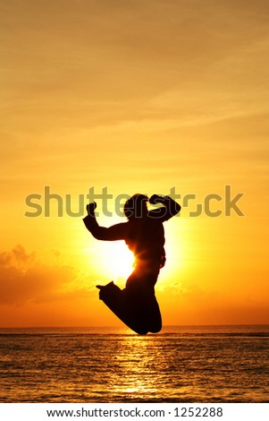 Silhouette of happy woman jumping at beach