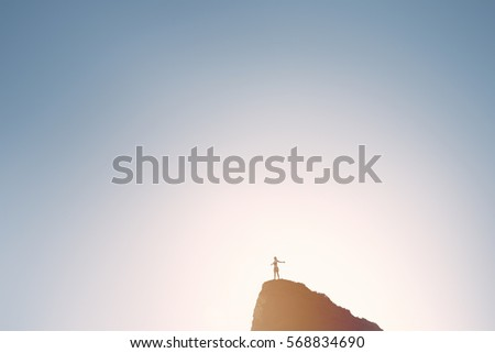 Silhouette of happy woman wearing skirt standing with outstretched arms on top of hill and celebrating achievement over sky and sun light on sunrise or sunset - inspiration concept with copy space