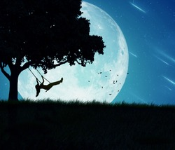Silhouette of happy young woman on a swing of a tree isolated on beautiful background of moon, earth, night skyline, falling stars. Body vitality, human spirit well being, freedom, happiness concept