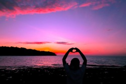 Silhouette of heart shape with hands colorful sunset at the sea beach
