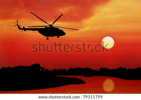 silhouette of helicopter fly over land and river during sunrise