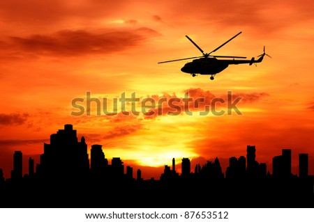 silhouette of helicopter fly over urban building