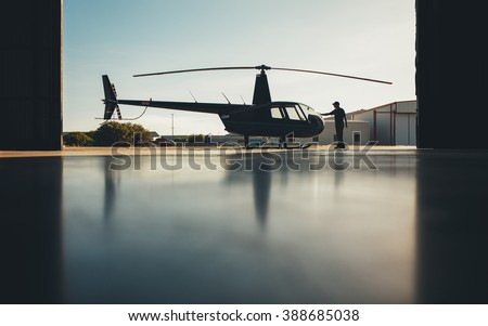 Silhouette of helicopter in the hangar with a pilot. Pilot doing preflight inspection of a helicopter.