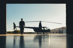 Silhouette of helicopter with a pilot in the airplane hangar. Pilot walking away from helicopter parked outside the hangar.