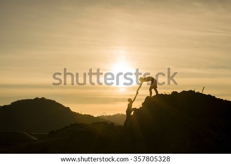Silhouette of helping hand on mountains in sunset background. #357805328