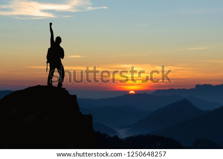 Silhouette of hiker man on top of mountain. successful people concept