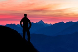 Silhouette of Hiker Man standing on Mountain watching majestic blue mountain ranges silhouettes with pink violet clouds. Sunrise in early morning. Allgau, Tirol, Austria, Alps.