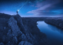 Silhouette of hiker with flashlight on a cliff over the river under the starry night sky.