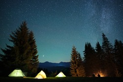 Silhouette of hikers resting besides burning bonfire near illuminated tourist tents on camping site in dark mountains under night sky with sparkling stars. Active lifestyle and outdoor living concept.