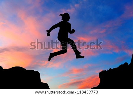 Silhouette of hiking woman jumping over the mountains at sunset